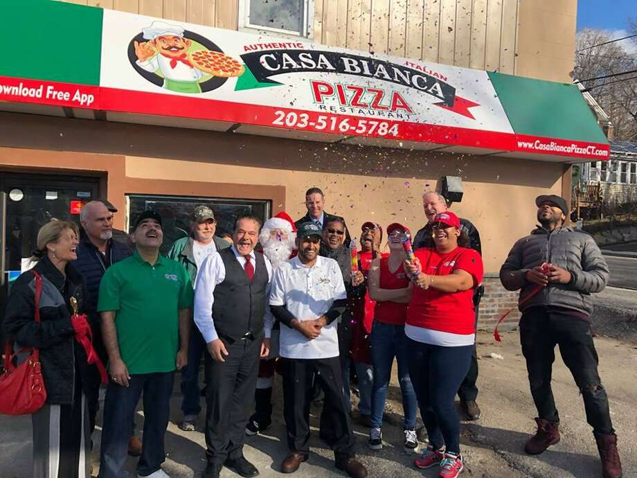 Mayor David Cassetti, center, celebrates with city officials and staff of newly opened Casa Bianca Pizza on Main Street Photo: Ansonia City Hall