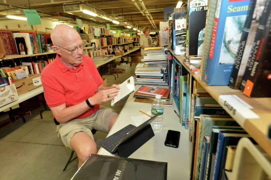 Volunteer Dave Hull looks up information online on the books he is sorting in his section of sports, business and transportation related books as staff and volunteers prepared the thousands of books for last weekend's Awesome Autumn Book Sale at the Wilton Library. Photo: Alex Von Kleydorff / Hearst Connecticut Media / Norwalk Hour