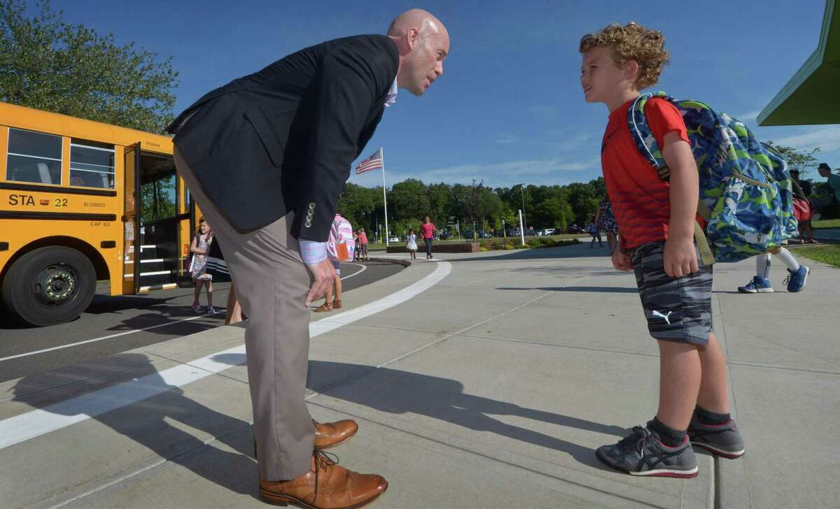 Assistant Principal Jeremy Cross helps Miller Driscoll students make their way to their first day of school including first grader Sam Thompson on Tuesday in Wilton.