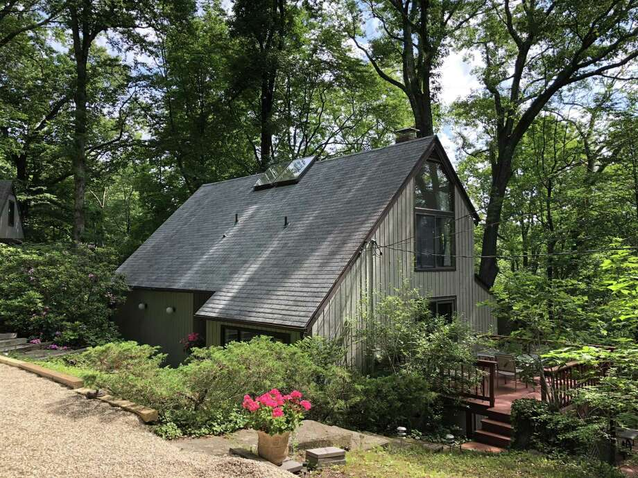 The residents of the gray contemporary house at 100 Chicken Street feel as if they live in a treehouse because it was built into a hillside in and among many trees. Photo: Contributed Photos