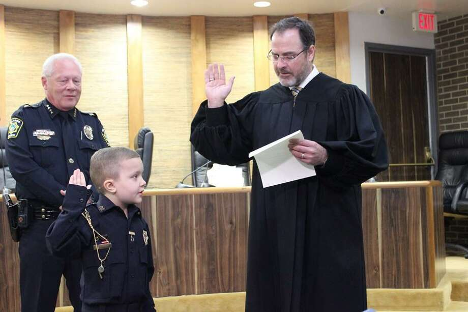 Bellaire Police Chief Byron Holloway watches as Judge Jerel Twyman swears in Officer Max Boatwright. Max has been fighting cancer since 2016 and loves to arrest criminals when he needs to. Photo: Courtesy Photo By Bellaire Police Department