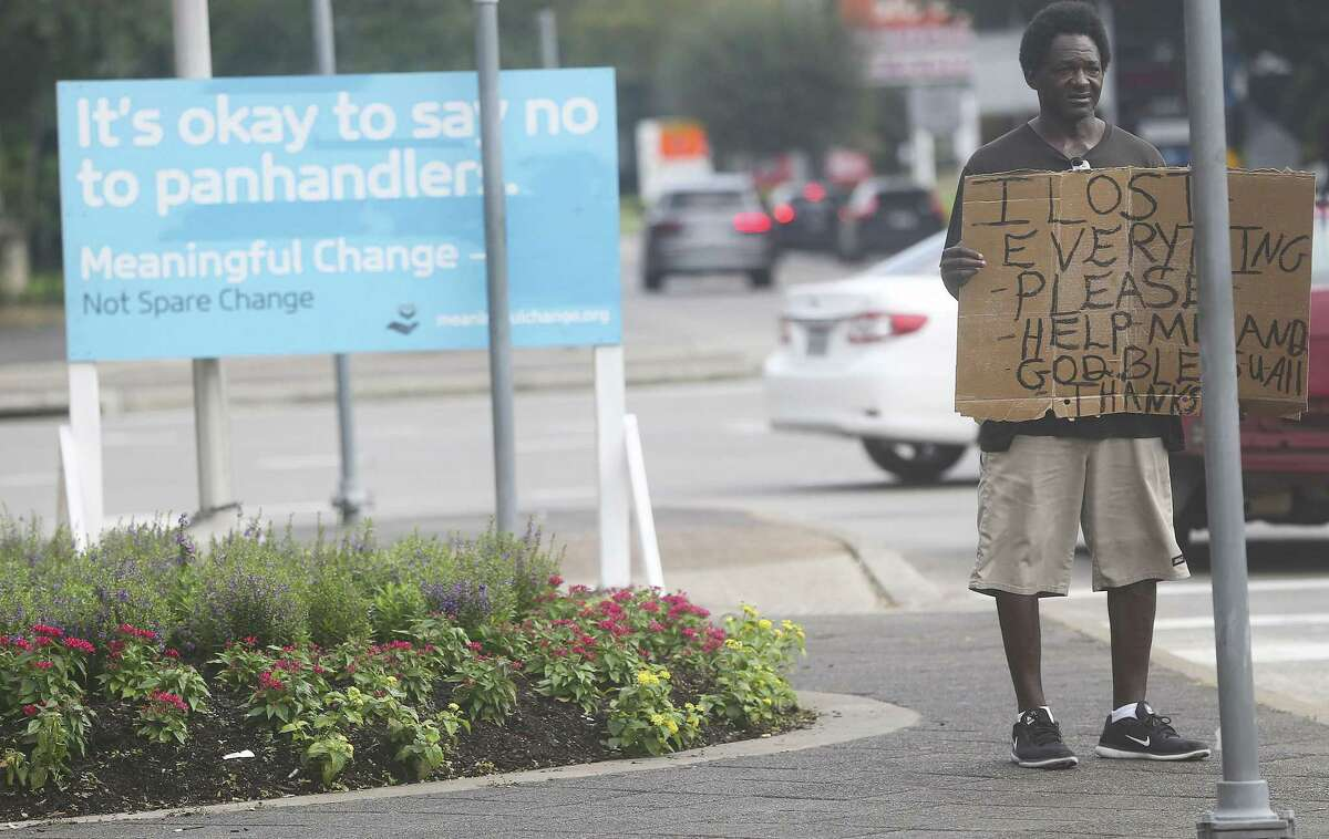 Tyron Davis panhandles despite a sign asking people not to give money near 610 and Westheimer on Friday, Sept. 21, 2018 in Houston.