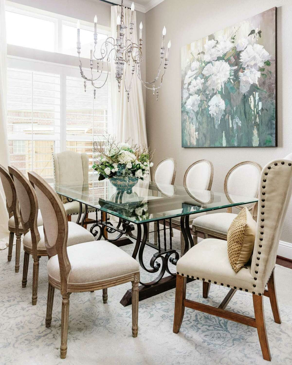 The dining room got a big makeover. While the Whites kept their glass-topped table, they added new window treatments, chairs, chandelier, rug and a large painting.