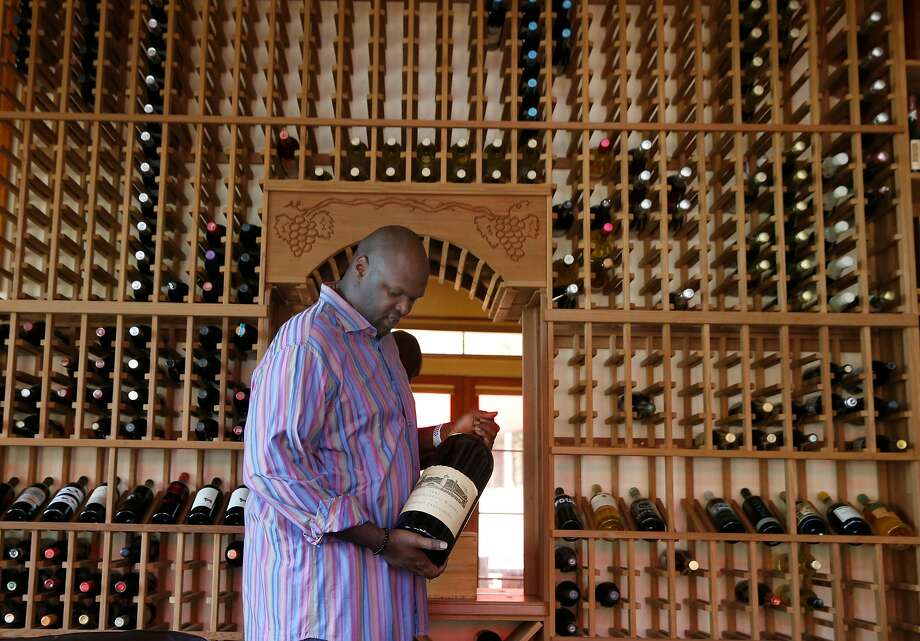 Adonal Foyle, in his wine cellar at home in Orinda, purchased a large-format Robert Mondavi bottle after signing his contract with the Golden State Warriors in 1997. Foyle has been a wine collector for decades. Photo: Paul Chinn / The Chronicle