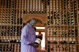 Former Golden State Warriors basketball player Adonal Foyle holds a large bottle of wine, that he purchased after signing his first professional contract, which is a centerpiece of an extensive wine collection at his home in Orinda, Calif. on Wednesday, Nov. 14, 2018.