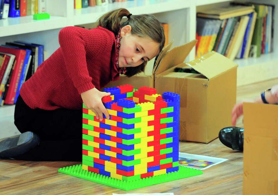 Hinda Landa, 10, who is with Chabad of Fairfield, works to build a base for a menorah made entirely out of Legos in preparation to celebrate Hanukkah in Fairfield, Conn. on Friday Nov. 30, 2018. The Lego menorah will be lit on Sunday as part of the Hanukkah celebration in downtown Fairfield. Photo: Christian Abraham / Christian Abraham / Connecticut Post