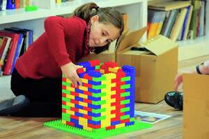 Hinda Landa, 10, who is with Chabad of Fairfield, works to build a base for a menorah made entirely out of Legos in preparation to celebrate Hanukkah in Fairfield, Conn. on Friday Nov. 30, 2018. The Lego menorah will be lit on Sunday as part of the Hanukkah celebration in downtown Fairfield.