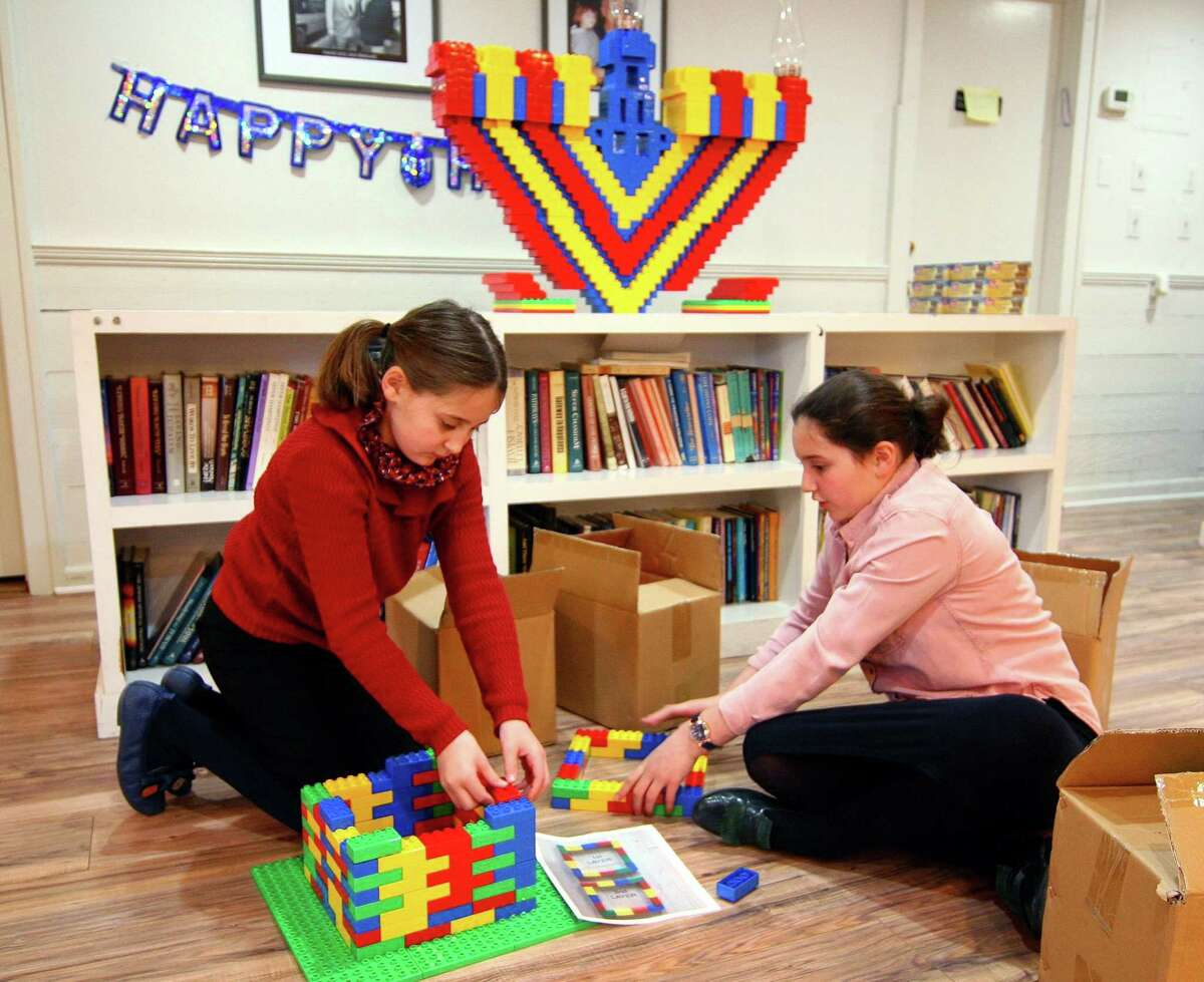 Hinda Landa, 10, left, and her sister Mushka, 11, who are with Chabad of Fairfield, work to build a base for a menorah made entirely out of Legos in preparation to celebrate Hanukkah in Fairfield, Conn. on Friday Nov. 30, 2018.The Lego menorah will be lit on Sunday as part of the Hanukkah celebration in downtown Fairfield.