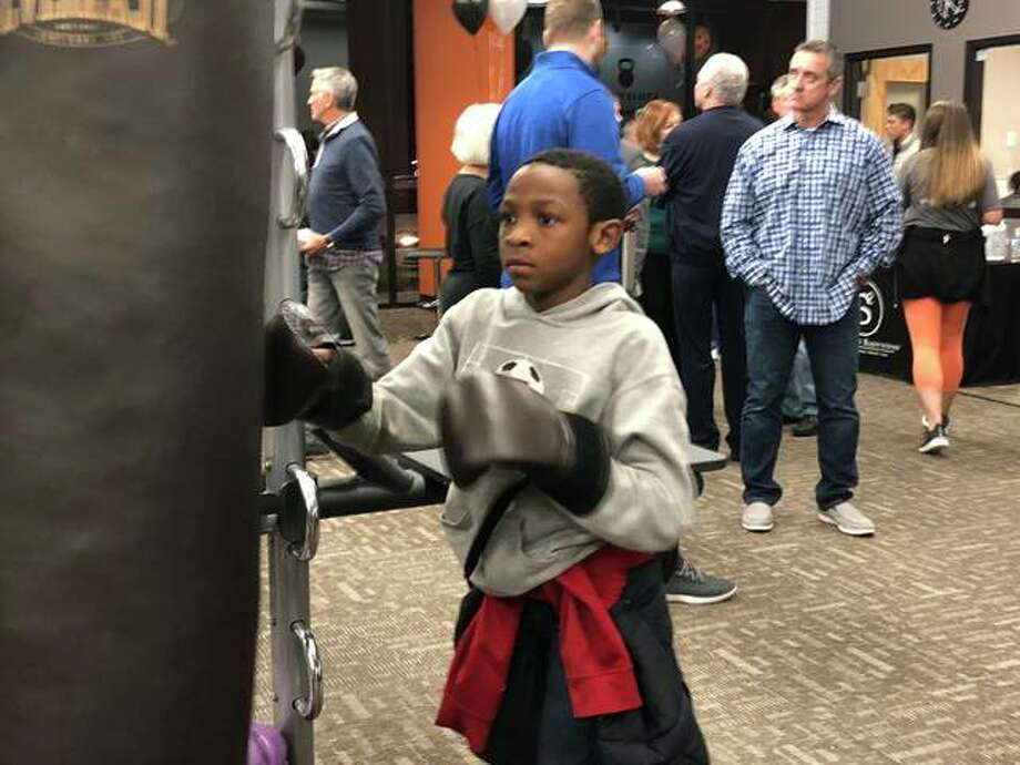 The E'Ville Fitness, located at 233 Harvard Drive, hosted a grand opening event Thursday evening, allowing guests of all ages to try out the equipment at the facility. One youngster, pictured, works on the punching bag. Community members gathered at the facility for an evening of food and door prizes, all while visiting various athletic and healthcare vendors. The gym had to reschedule its grand opening event due to inclement weather in November. Photo: Photos By Julia Biggs | The Intelligencer
