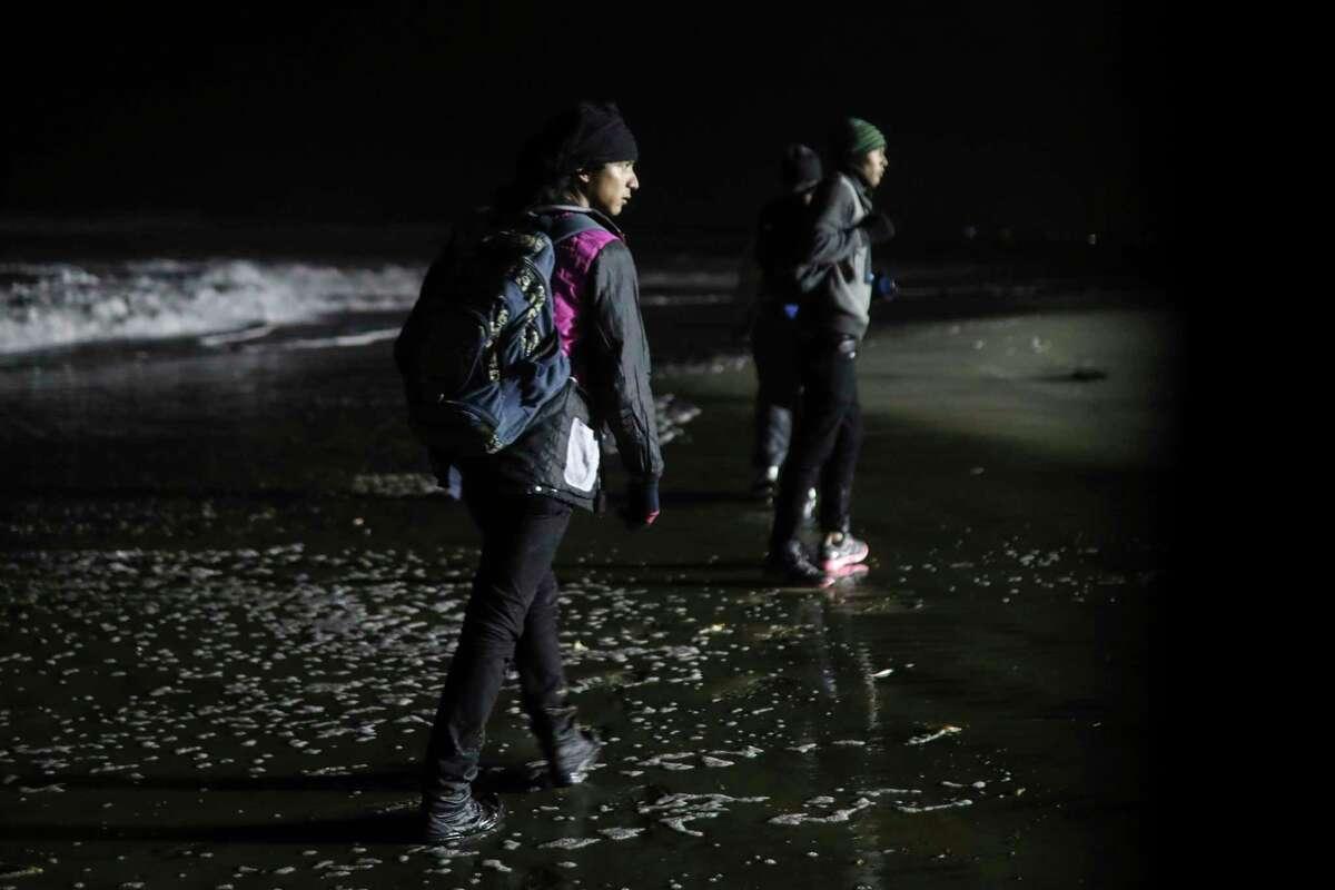 Honduran migrants walk onto U.S. territory after crossing the border wall from Tijuana, Mexico, Friday, Nov. 30, 2018.