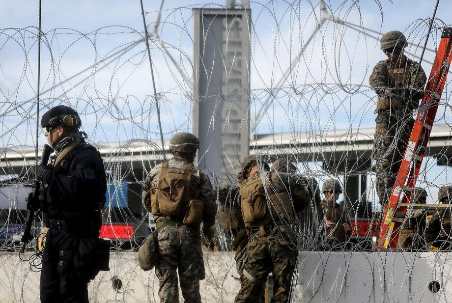 A Customs and Border Protection agent (left) stands guard as U.S. troops erect concertina wire at the San Ysidro port of entry in San Diego County on Nov. 22. Troop levels will soon drop. Photo: Mario Tama / Getty Images