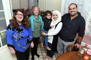 Aminah, center right, with her daughter, Retaj, 4, and husband, Issa, right, are photographed in the kitchen of their home in New Haven with Jean Silk, center left, coordinator of Jewish Community Alliance for Refugee Resettlement, and Gilah Benson-Tilsen, left, JCARR team leader Congregation Beth El-Keser Israel, on Nov. 28.