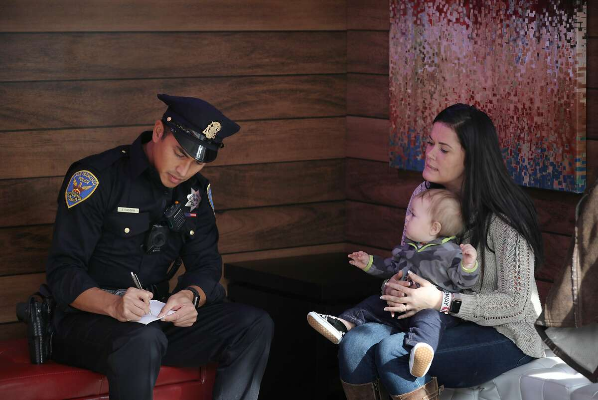 Natalie West (right) holds her 9-month old son Seven Snodgrass (center), both of Eureka, on her lap as she discusses the theft of her wallet out of her baby''s stroller with Officer Jason Castro (left) at the Union Square ice skating rink on Monday, November 26, 2018 in San Francisco, Calif.