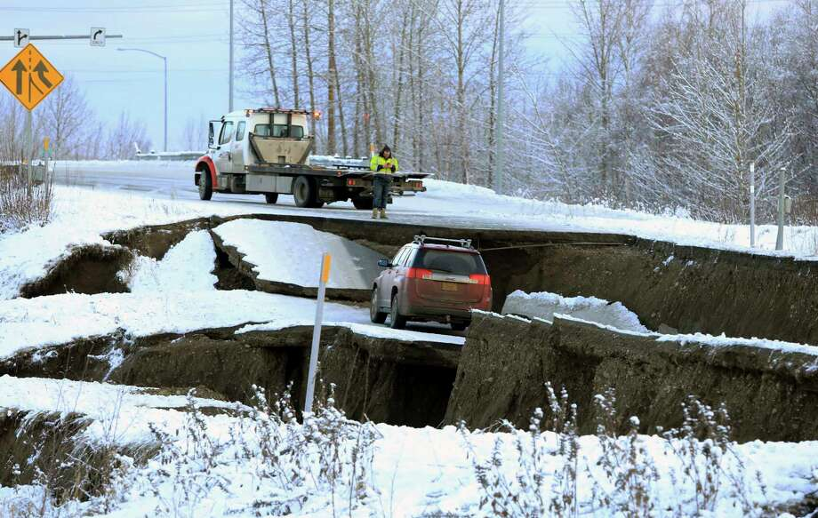 A tow truck driver assesses a car stuck on a section of an off-ramp that collapsed during an earthquake Friday morning, Nov. 30, 2018 in Anchorage, Alaska. The driver was not injured attempting to exit Minnesota Drive at International Airport Road. Back-to-back earthquakes measuring 7.0 and 5.8 rocked buildings and buckled roads Friday morning in Anchorage, prompting people to run from their offices or seek shelter under office desks, while a tsunami warning had some seeking higher ground. (AP Photo/Dan Joling) Photo: Dan Joling / Copyright 2018 The Associated Press. All rights reserved.