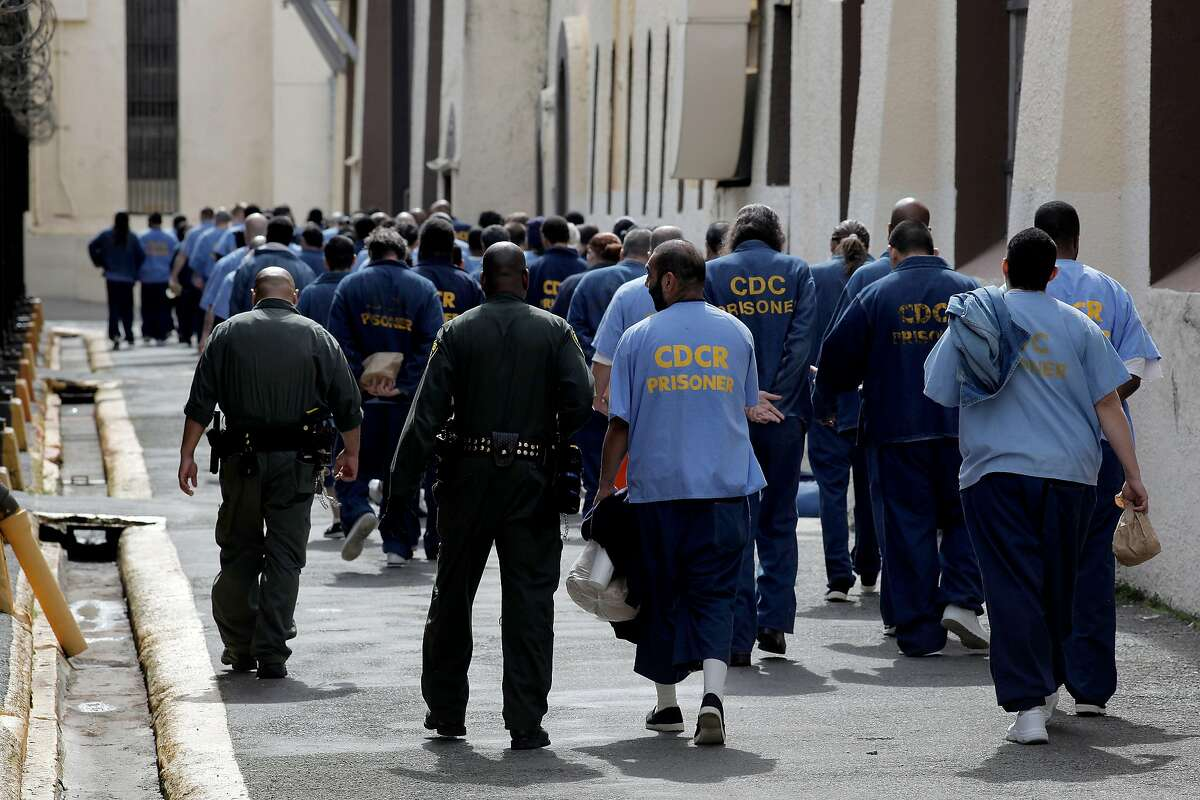 Corrections officers, lead prisoners back to their housing inside San Quentin State Prison, on Friday Mar. 4, 2011, in San Quentin, Ca. California State prison guards and their supervisors, have racked up an astounding 33 million hours of vacation, sick and other paid time off, which could amount to as much as a $1 billion liability for the state. A Senate report warned, a year ago, that mandatory furloughs at a 24-7 agency, would lead to such future burdens.
