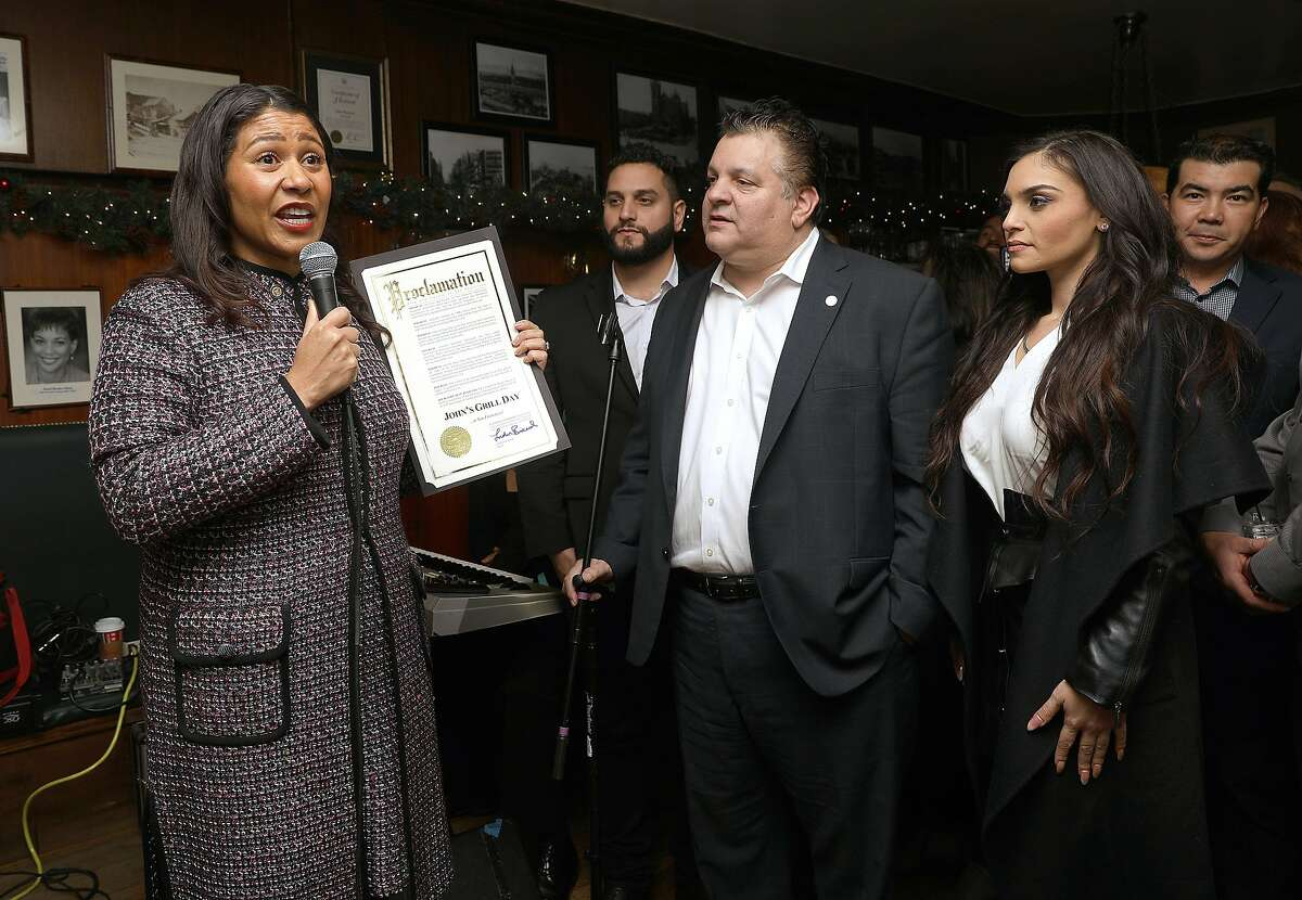 Mayor London Breed (left) announces creating an official John's Grill day as John's Grill celebrates its 110th anniversary on Thursday, Nov. 29, 2018, in San Francisco, Calif. At right is owner John Konstin.