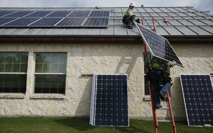 Workers install solar panels on a home in 2012. A plan by CPS Energy to rework its solar rebate program will halve residential rebates and drastically cut back commercial solar incentives.
