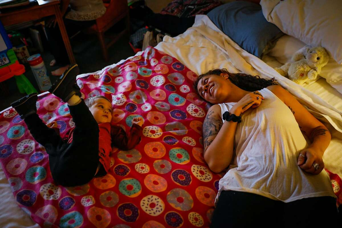 Camp Fire evacuees Brook Madison (right) plays with her son Justin Madison's, 1, at the hotel they've been living in, in Woodland, California, on Wednesday, Nov. 28, 2018. Brook and her mother Jaki lost their homes in the Camp Fire but Jaki's cafe was spared.