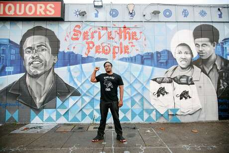Artist Senay Dennis, who will paint the Oscar Grant mural, stands in front of his mural in West Oakland that honors Huey Newton and the Black Panther Party. Photo: Michael Short / Special To The Chronicle