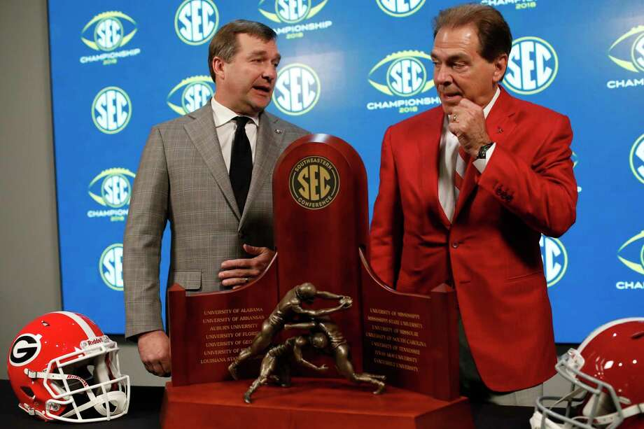 Georgia head coach Kirby Smart, left, and Alabama head coach Nick Saban talk near the Championship trophy, Friday, Nov. 30, 2018, in Atlanta. Georgia and Alabama will play Saturday in the Southeastern Conference championship NCAA college football game. (Joshua L. Jones, Athens Banner-Herald via AP) Photo: Joshua L. Jones / Athens Banner-Herald