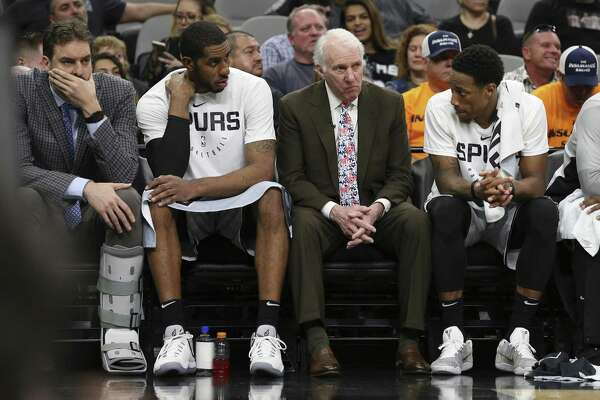 Spurs head coach Gregg Popovich (center) sits with Spurs' LaMarcus Aldridge (left) and DeMar DeRozan (right) near the end of the game against the Houston Rockets at the AT&T Center on Friday, Nov. 30, 2018. Rockets defeated the Spurs, 136-105. (Kin Man Hui/San Antonio Express-News)