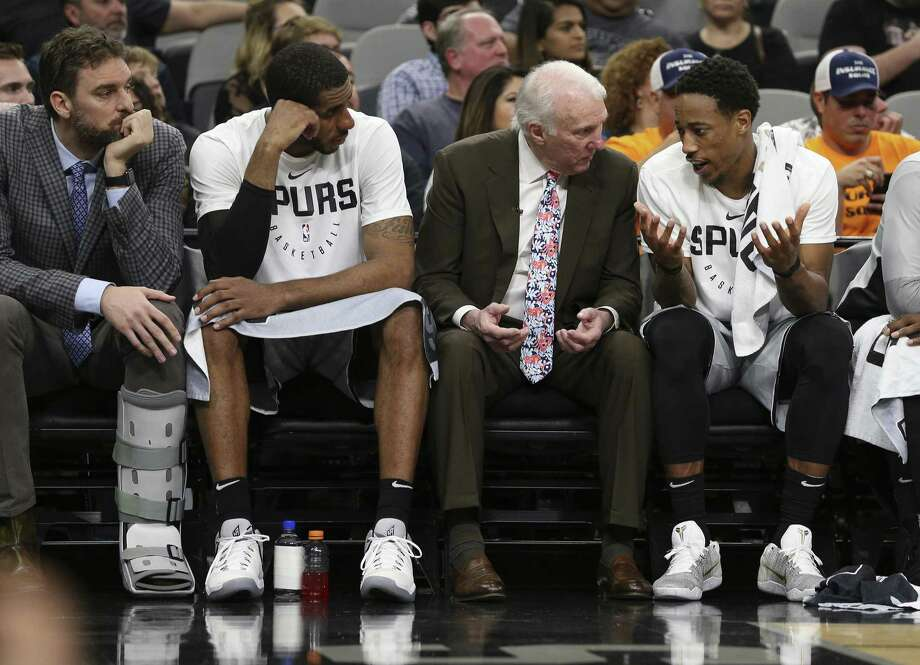 Spurs head coach Gregg Popovich (center) sits with DeMar DeRozan (right) and LaMarcus Aldridge (left) near the end of the game against the Houston Rockets at the AT&T Center on Friday, Nov. 30, 2018. Rockets defeated the Spurs, 136-105. (Kin Man Hui/San Antonio Express-News) Photo: Kin Man Hui, Staff Photographer / San Antonio Express-News / ©2018 San Antonio Express-News