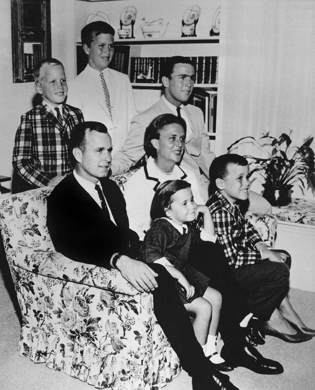 George H.W. Bush sits on couch with his wife Barbara and their children in 1964. George W. Bush sits at right behind his mother. Behind couch are Neil and Jeb Bush. Sitting with parents are Dorothy and Marvin Bush.