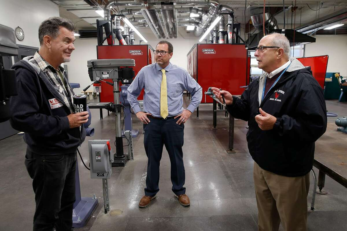 Potential teacher applicant Mark Metz (left) tours the new welding and metal shop classroom with assistant principal Andrew Brooks (center) and Mike Peritz, a retired instructor at Kennedy High School in Richmond, Calif. on Thursday, Nov. 29, 2018. After a teaching position for the welding program remained unfilled, retired teacher Mike Peritz sent out an email pleading with the community to find applicants. His request went viral and now several potential candidates have come forward.