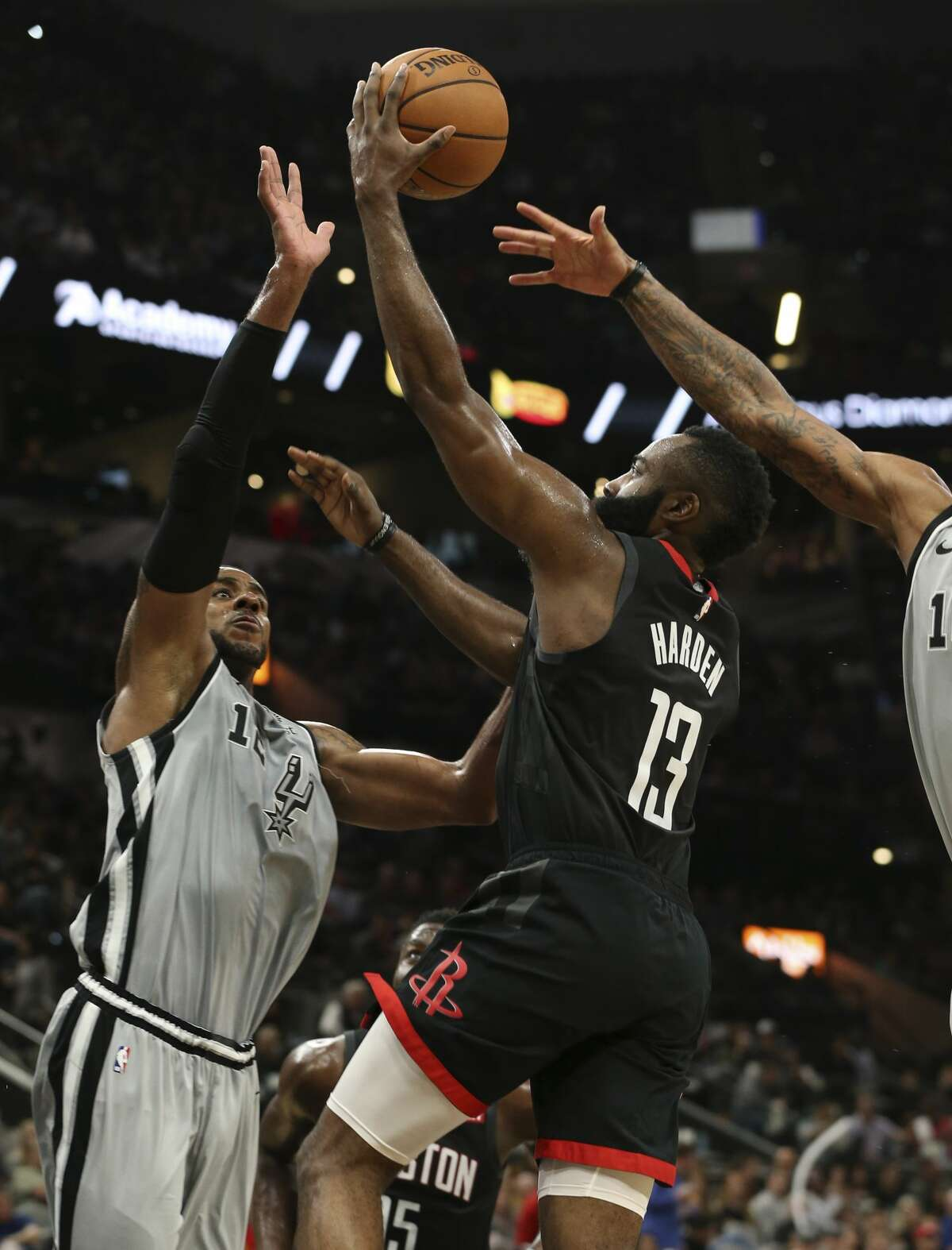 Houston Rocket's James Harden (13) goes up for a shot against Spurs' LaMarcus Aldridge (12) and DeMar DeRozan (10) in the second half at the AT&T Center on Friday, Nov. 30, 2018. Rockets defeated the Spurs, 136-105. (Kin Man Hui/San Antonio Express-News)