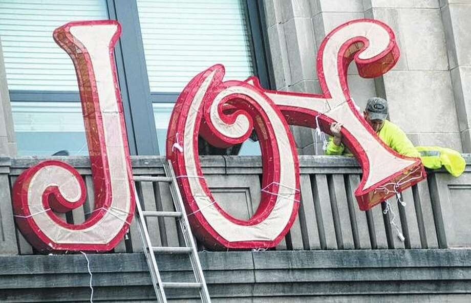 A worker from the Hazleton, Pennsylvania, Department of Public Works hangs joy from the front of City Hall as he and his coworkers decorate the building for the holiday season.