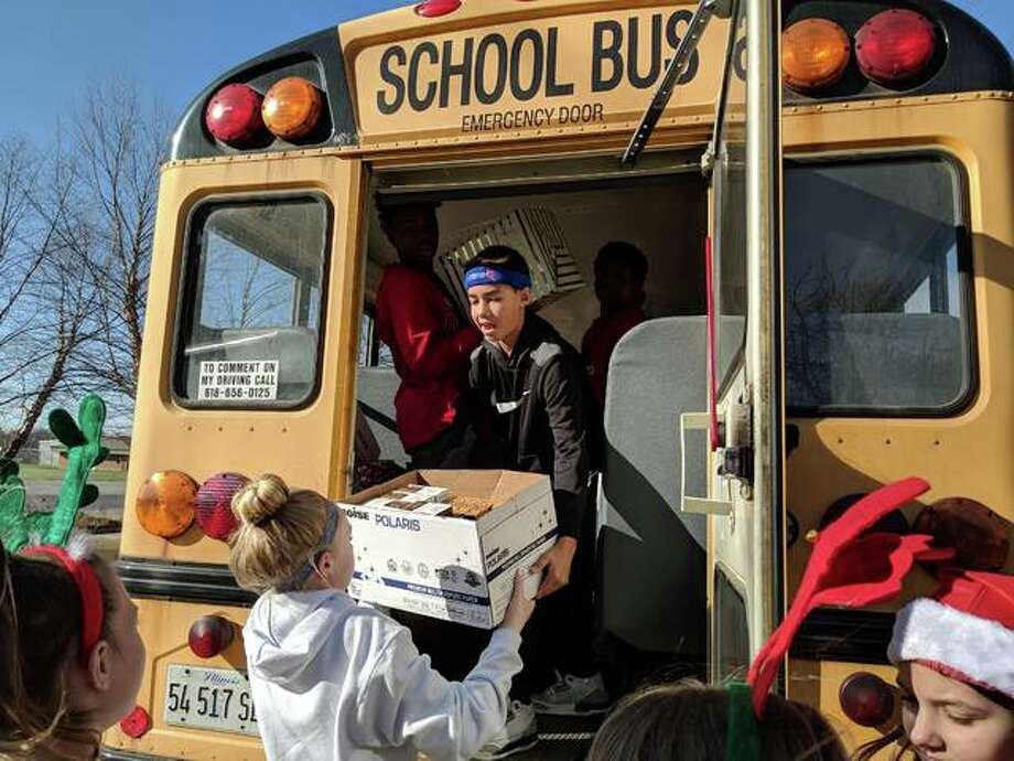 Liberty and Lincoln middle school students pack up a busload of canned food and toys that they collected in last year's LMS Toy and Food Drive. This year, Friends In Touch (FIT) and Guidance in Operation (GO) are currently collecting donations, new toys, and non-perishable food through Dec. 11 as a part of their annual efforts. Photo: For The Intelligencer