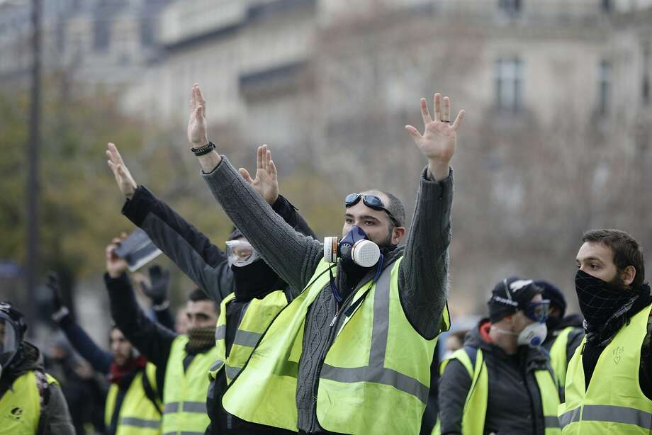Yellow jacket protesters gather near the Champs-Elysees in Paris. Many clashed with police. Photo: Kamil Zihnioglu / Associated Press
