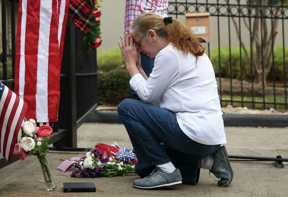 Suzette Renee Drab says a prayer after leaving a flower bouquet at the gate outside of former President George H.W. Bush's residence on Saturday, Dec. 1, 2018, in Houston. Bush passed away on Friday at the age of 94. Photo: Yi-Chin Lee, Staff Photographer / © 2018 Houston Chronicle