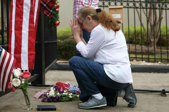Suzette Renee Drab says a prayer after leaving a flower bouquet at the gate outside of former President George H.W. Bush's residence on Saturday, Dec. 1, 2018, in Houston. Bush passed away on Friday at the age of 94.