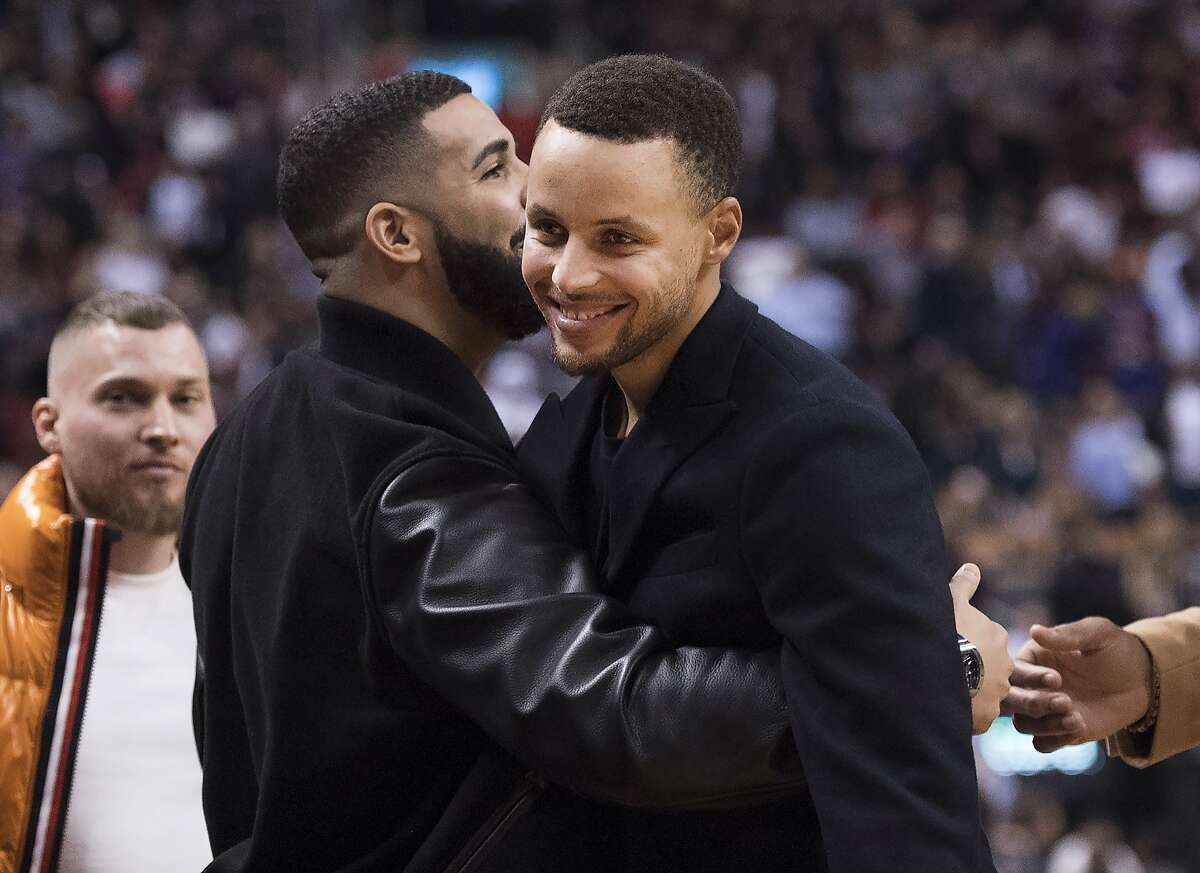 Rapper Drake, left, hugs Golden State Warriors guard Stephen Curry during first half of NBA basketball between the Warriors and the Toronto Raptors in Toronto on Thursday, Nov. 29, 2018. (Nathan Denette/The Canadian Press via AP)