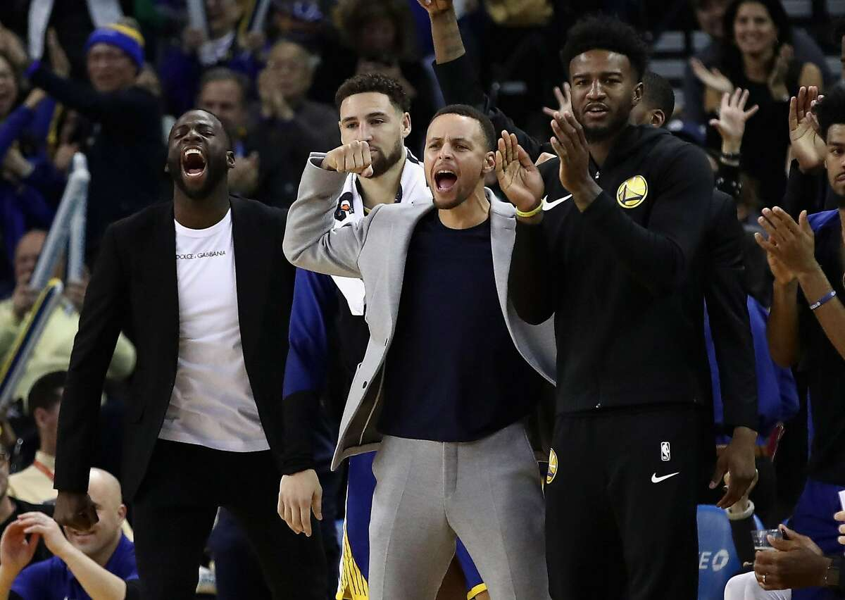 OAKLAND, CA - NOVEMBER 26: Draymond Green #23, Stephen Curry #30, and Jordan Bell #2 of the Golden State Warriors react on the bench after the Warriors made a basket duirng their game against the Orlando Magic at ORACLE Arena on November 26, 2018 in Oakland, California. NOTE TO USER: User expressly acknowledges and agrees that, by downloading and or using this photograph, User is consenting to the terms and conditions of the Getty Images License Agreement. (Photo by Ezra Shaw/Getty Images)