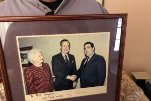 Burgdorf, 63 poses with a photo of his meeting with President George H.W. Bush and First Lady Barbara Bush after he aided in H.W.'s 1980 and 1988 runs for president. Burgdorf served at Bush's Capital Region campaign coordinator for the 1988 election.