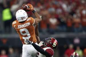 ARLINGTON, TEXAS - DECEMBER 01:  Collin Johnson #9 of the Texas Longhorns makes a pass reception against Tre Brown #6 of the Oklahoma Sooners in the first quarter at AT&T Stadium on December 01, 2018 in Arlington, Texas.