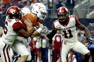 ARLINGTON, TEXAS - DECEMBER 01:  Sam Ehlinger #11 of the Texas Longhorns runs for a touchdown against Tre Brown #6 and Parnell Motley #11 of the Oklahoma Sooners in the first quarter at AT&T Stadium on December 01, 2018 in Arlington, Texas.