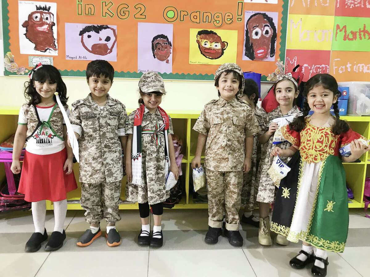 For Flag Day on Nov. 1, pre-school children in the United Arab Emirates wear traditional dresses, camouflage outfits, and hair ribbons of red, black, green and white, the colors of the UAE flag.