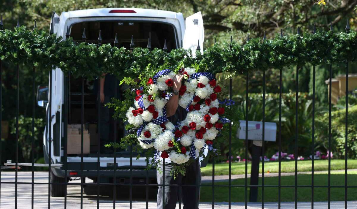 The Senterpiece owner Ken Senter works on putting a presidential wreath on the gate outside of former President George H.W. Bush's residence on Saturday, Dec. 1, 2018, in Houston. Bush passed away on Friday at the age of 94. The Senterpiece also put on the wreaths for Mrs. Barbara Bush when she passed away earlier this year.