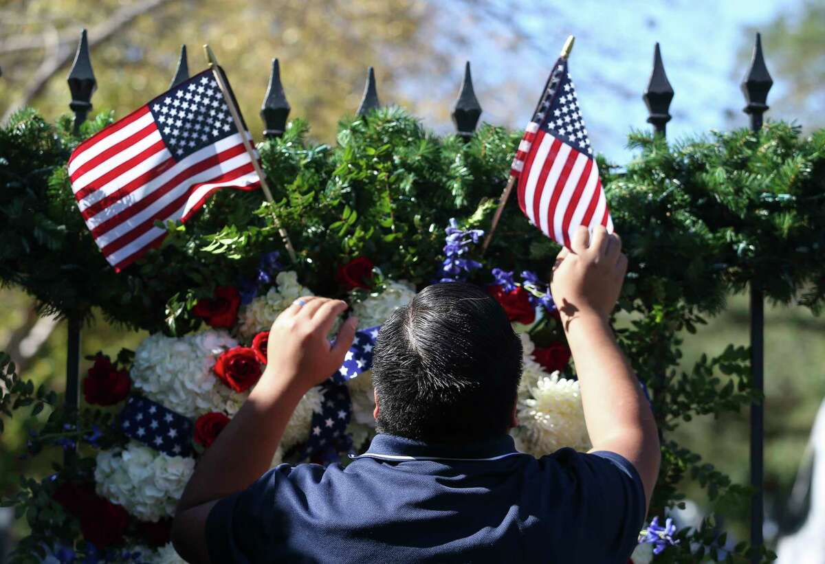 The Senterpiece worker Erick Herrera makes sure the two small American flags are placed correctly on th presidential wreath on the gate outside of former President George H.W. Bush's residence on Saturday, Dec. 1, 2018, in Houston. Bush passed away on Friday at the age of 94. The Senterpiece also put on the wreaths for Mrs. Barbara Bush when she passed away earlier this year.