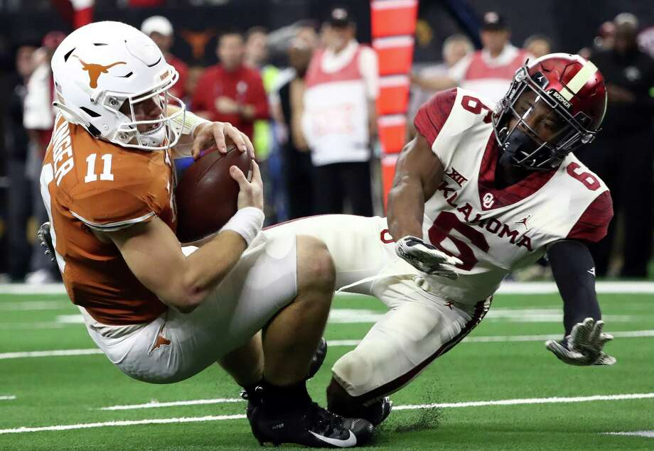 ARLINGTON, TEXAS - DECEMBER 01:  Sam Ehlinger #11 of the Texas Longhorns is tackled by Tre Brown #6 of the Oklahoma Sooners for a safety in the fourth quarter at AT&T Stadium on December 01, 2018 in Arlington, Texas. Photo: Getty Images / 2018 Getty Images