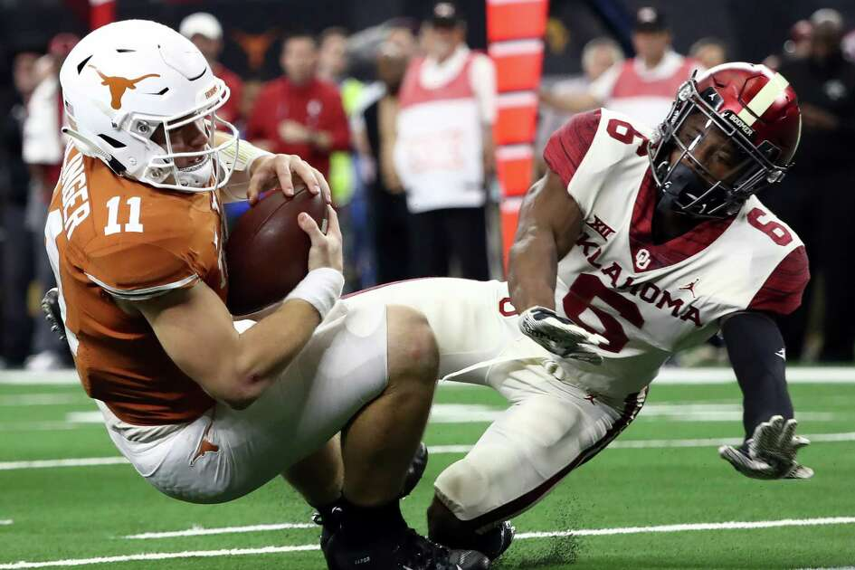 ARLINGTON, TEXAS - DECEMBER 01: Sam Ehlinger #11 of the Texas Longhorns is tackled by Tre Brown #6 of the Oklahoma Sooners for a safety in the fourth quarter at AT&T Stadium on December 01, 2018 in Arlington, Texas.