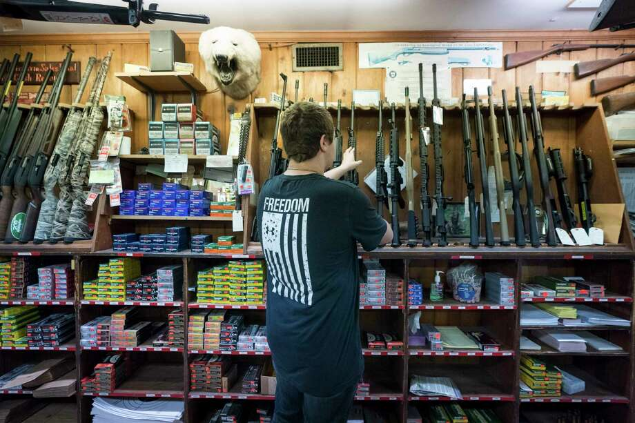 An employee handles a rifle for sale inside the Clark Brothers Gun Shop in Warrenton, Va., Feb. 25, 2018. Firearms sales have dropped during the Trump presidency. (Erin Schaff/The New York Times) Photo: ERIN SCHAFF / NYTNS