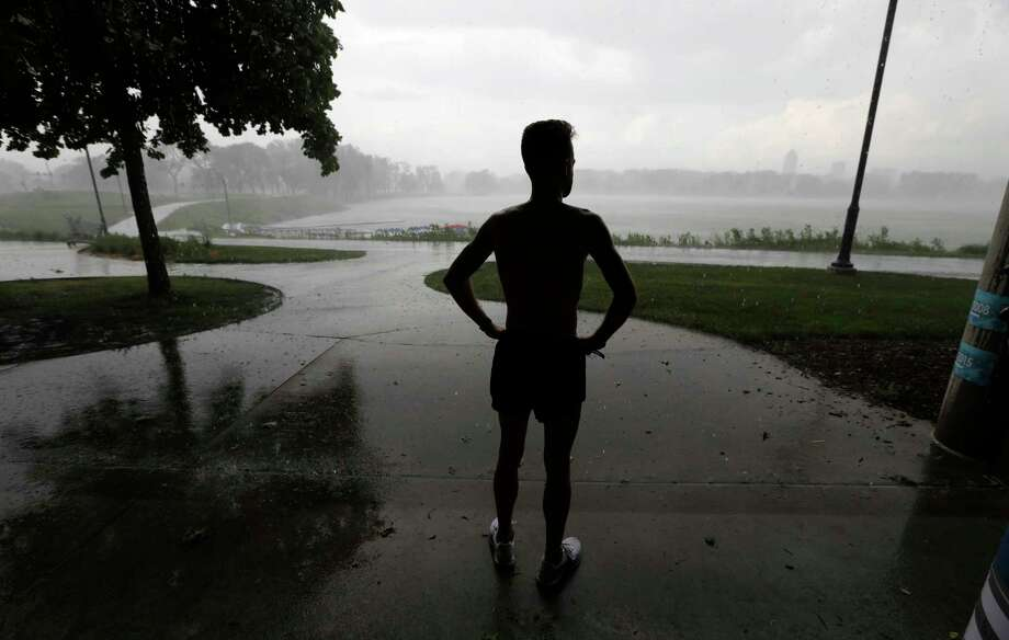 "FILE- In this May 29, 2018, file photo a man takes shelter from a rainstorm while running at Gray's Lake Park in Des Moines. Researchers have found dozens of unconscious biases that can drive people to make money decisions they later regret. These behavioral economics concepts include things like ""anchoring"", when a specific and perhaps arbitrary number you have in mind sways your decision-making. Or, the ""endowment effect"" can cause you to overvalue something simply because you own it, leading you to cling to a stock that's tanking. (AP Photo/Charlie Neibergall, File) Photo: Charlie Neibergall / Copyright 2018 The Associated Press. All rights reserved."
