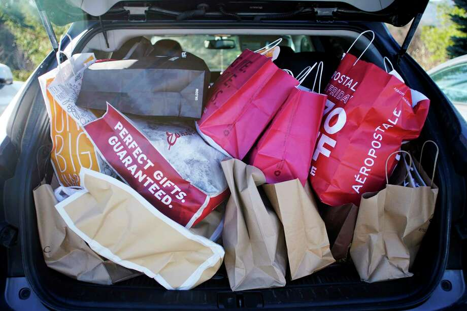 FILE- In this Nov. 23, 2018, file photo shopping bags are stuffed into a car at Prime outlets on Black Friday in Lee, Mass. Last year, 65 percent of millennial shoppers put gifts on their credit card. This year, roughly a third of them are still paying off that debt, according to an annual survey of holiday shoppers from NerdWallet. (Ben Garver/The Berkshire Eagle via AP, File) Photo: Ben Garver / The Berkshire Eagle
