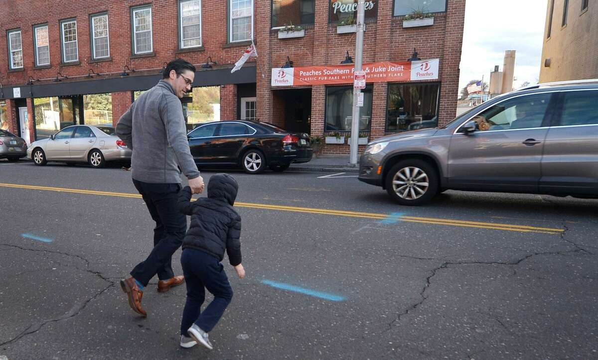 Pedestrians cross Wall Street where there is no crosswalk Wednesday, November 28, 2018, in Norwalk, Conn. The Norwalk Bike/Walk Commission is looking to get more crosswalks approved and installed throughout the city. Such efforts require review by city and often state engineers, who consider accident histories, posted speed limits and sight lines.