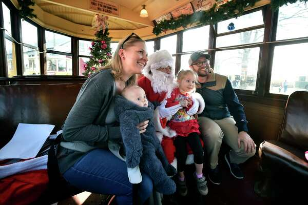 East Haven, Connecticut - Saturday, December 1, 2018: Mom Vicki Grubaugh of New Haven, her son Philip, 4-months, Santa and her daughter Sophie Grubaugh, 3, and father and father Nathan Grubaugh Saturday at the Shore Line Trolley Museum in East Haven during the Santa's Trolley Winter Wonderland. Santa's Trolley Winter Wonderland runs through December 16. Children can visit with Santa, have cookies and hot chocolate and view antique trolleys are decorated for the holidays.