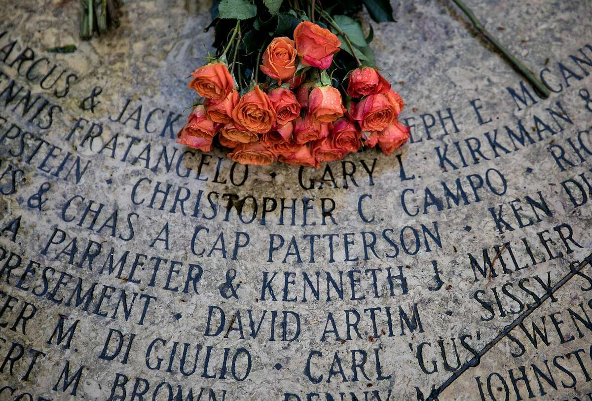Names are etched into the Circle of Friends near a bouquet of flowers placed during an observance of World Aids Day held at the National Aids Memorial Grove at Golden Gate Park in San Francisco, Calif. Saturday, Dec. 1, 2018.